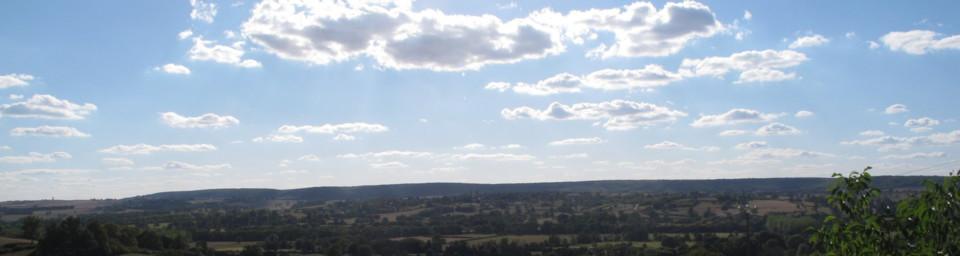 Photo prise depuis l'église Saint-Martin de Lys : au premier plan, le château de Lys, au second plan le château de Pignol, tous trois inscrits à l'inventaire des Monuments Historiques. Sur la crête boisée, un photomontage préfigurant cinq éoliennes qui devraient agrémenter le paysage.